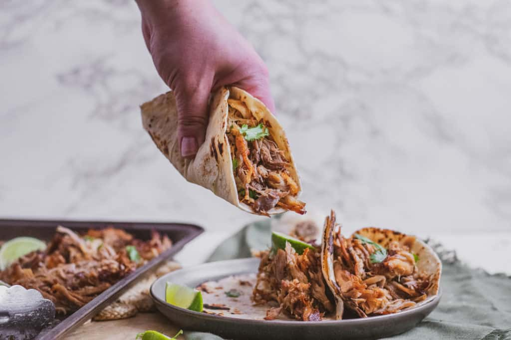 Low carb keto Instant pot pork carnitas in a tortilla on a black plate being picked up by a hand
