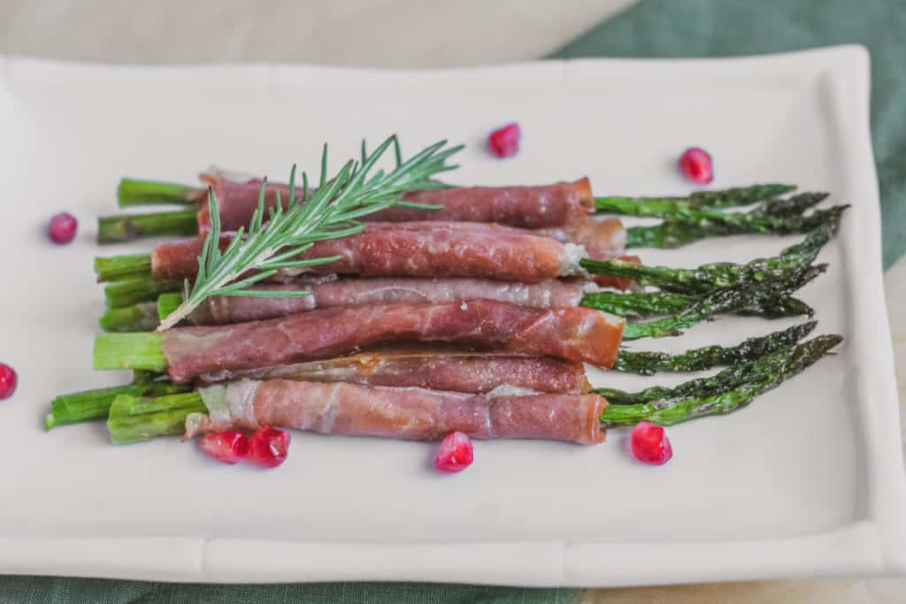 Keto prosciutto wrapped asparagus on a white plate.
