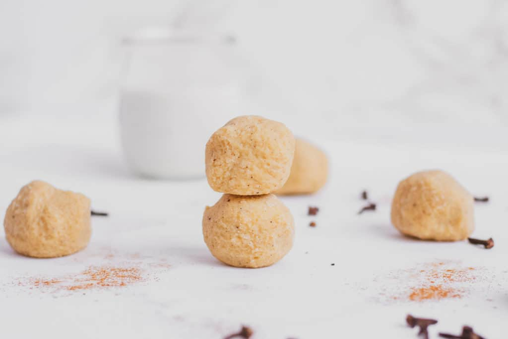 Keto ginger bread fat bombs on a white surface rolled in a ball.