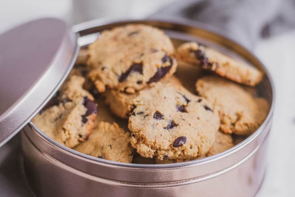 Keto Espresso Chocolate Chunk Cookies stacked on top of each other in a brass can on a white surface.