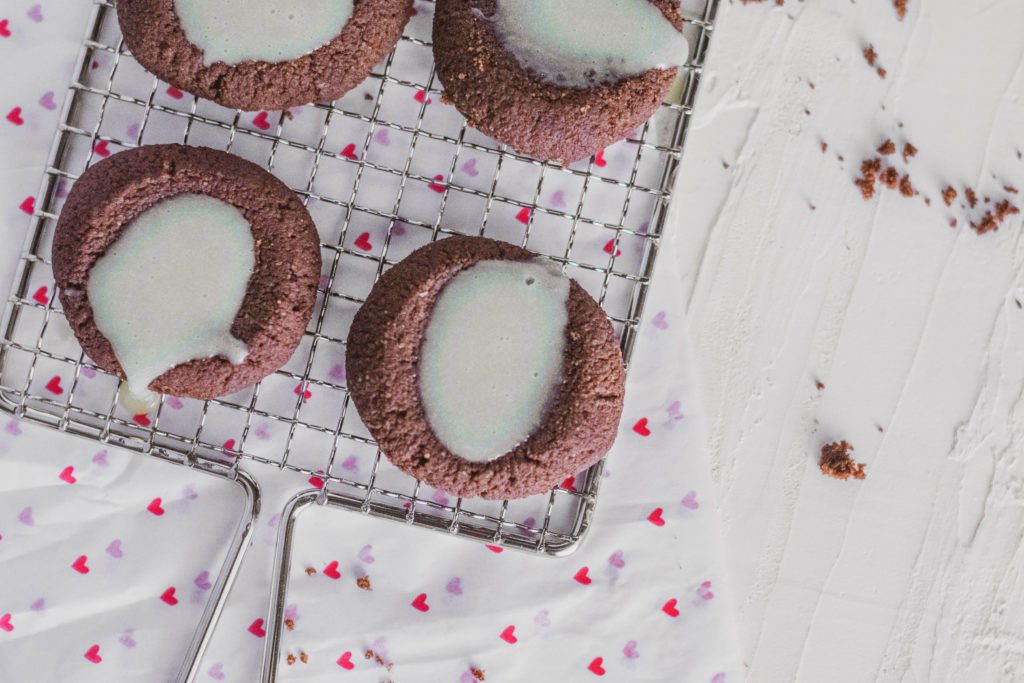 Keto Chocolate Thumbprint Cookies with white chocolate ganache in the middle on a wire wrack and heart paper on the bottom on a white surface.