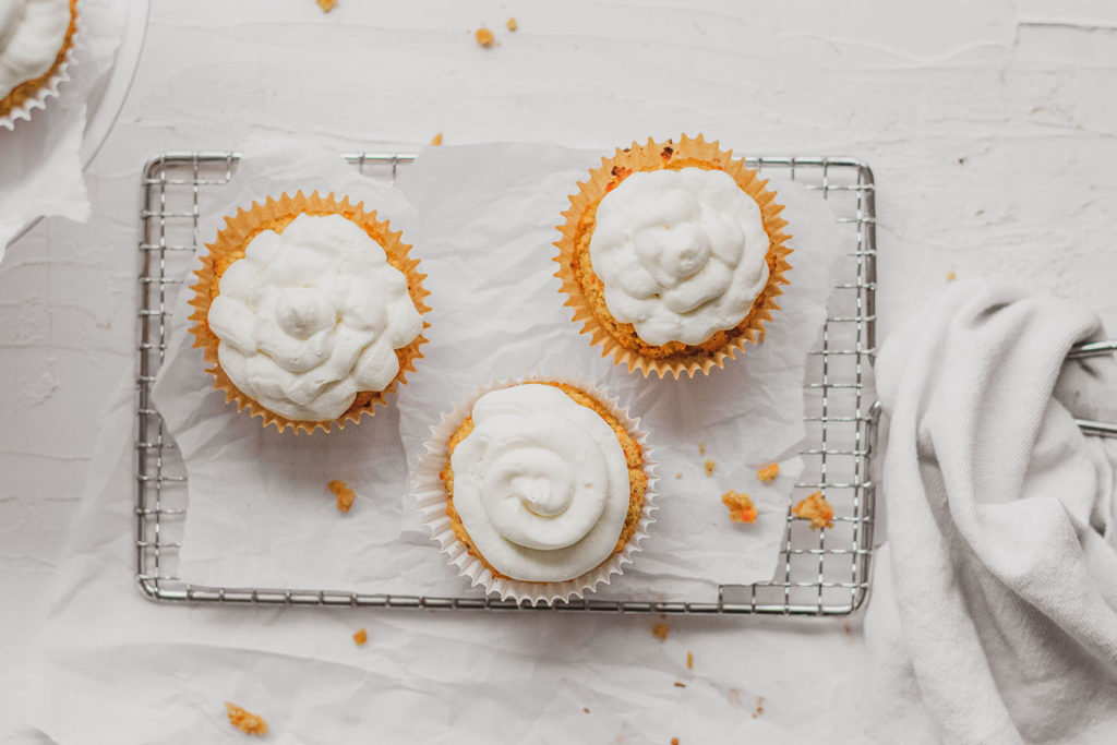 Keto carrot cake muffins with cream cheese frosting on a wire wrack on a white surface.