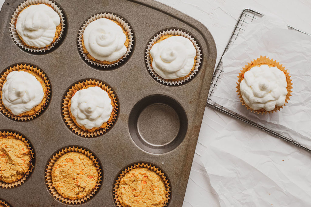 Keto carrot cake muffins with cream cheese frosting in a muffin pan.