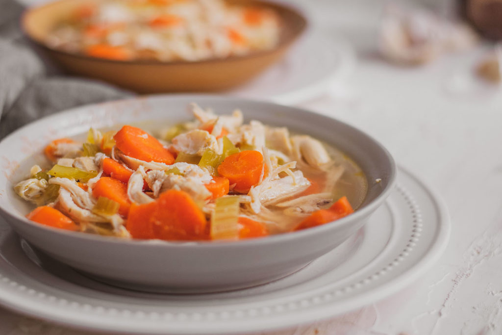 Keto chicken soup with carrots and celery in a white bowl on a white surface.