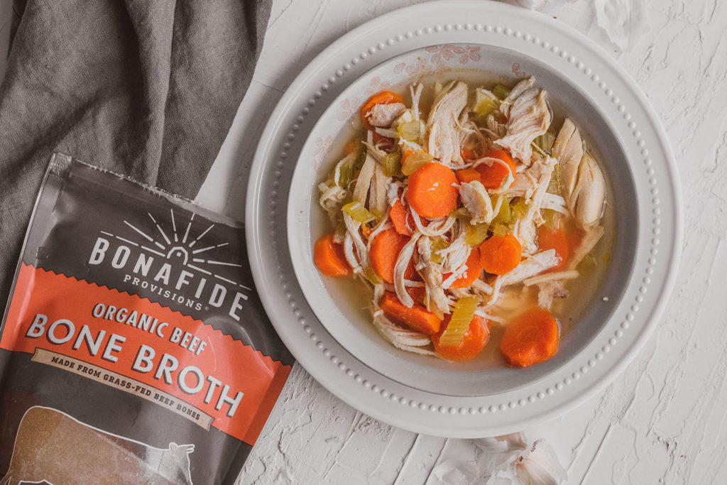 Keto chicken soup with carrots and celery in a white bowl on a white surface with a bag of Bonafide Provisions bone broth on the side.