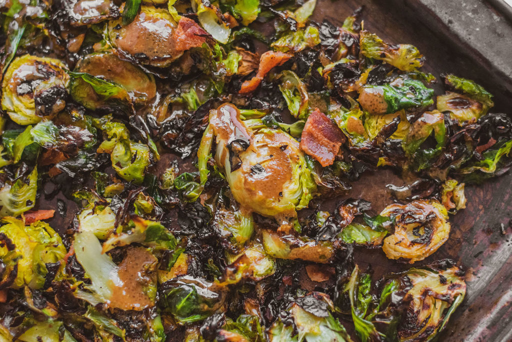 Crispy keto honey mustard Brussels sprouts with bacon on a sheet pan with hands drizzling the sauce on top.