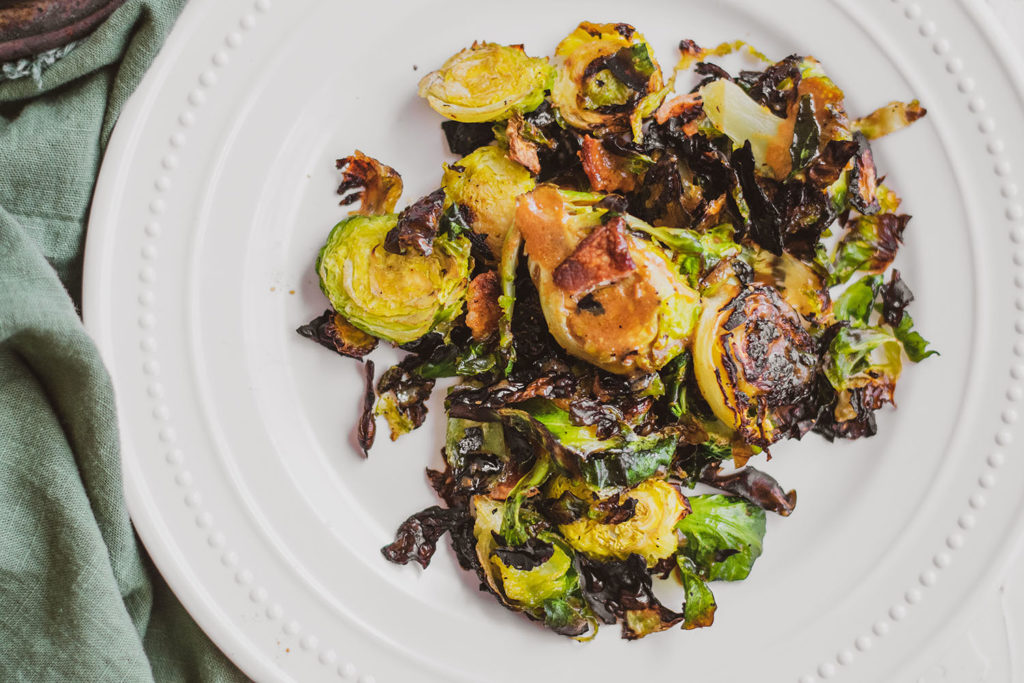 Crispy keto honey mustard Brussels sprouts with bacon on a white plate and a green napkin on the side.