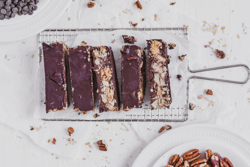Keto chocolate peanut butter crunch bars on a wire wrack on a white surface.