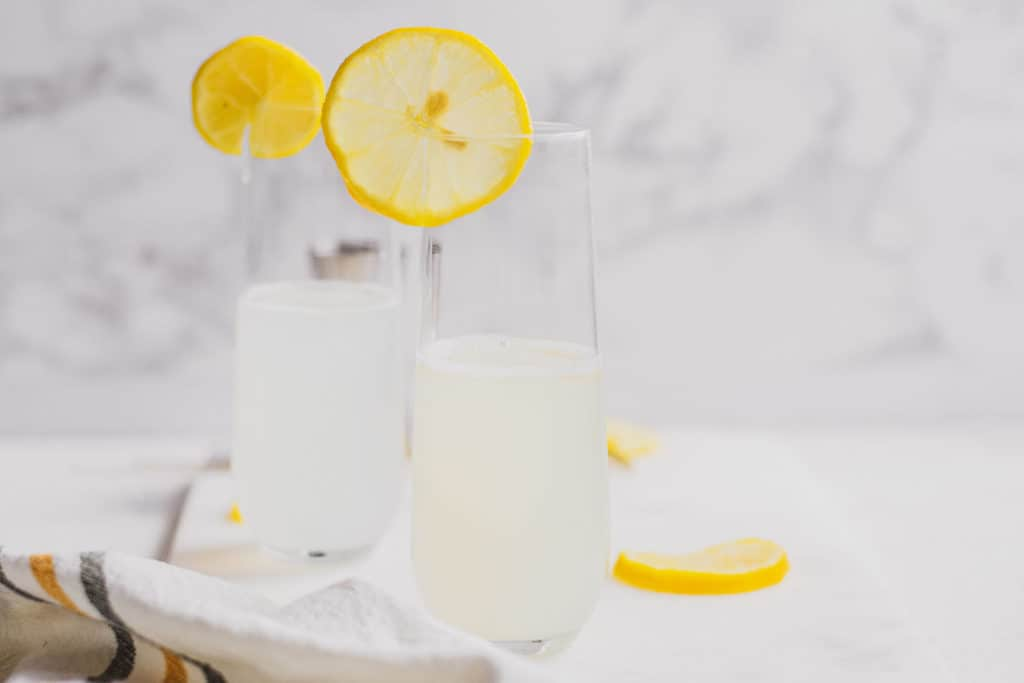 Keto Lemon Drop Cocktail in a clear glass on a white surface with lemon slices.