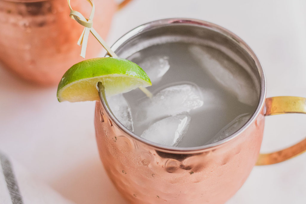 Keto Moscow Mule in brass mugs with a lime slice on the rim on a white surface.