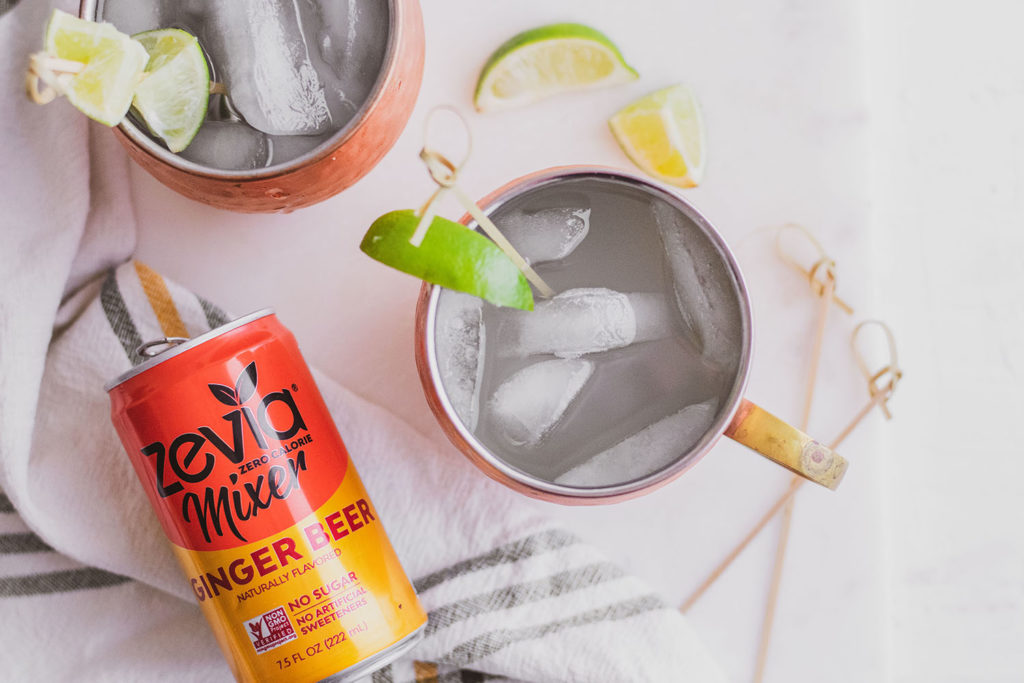 Keto Moscow Mule in brass mugs with a lime slice on the rim on a white surface and a Zevia ginger beer mixer on the side.