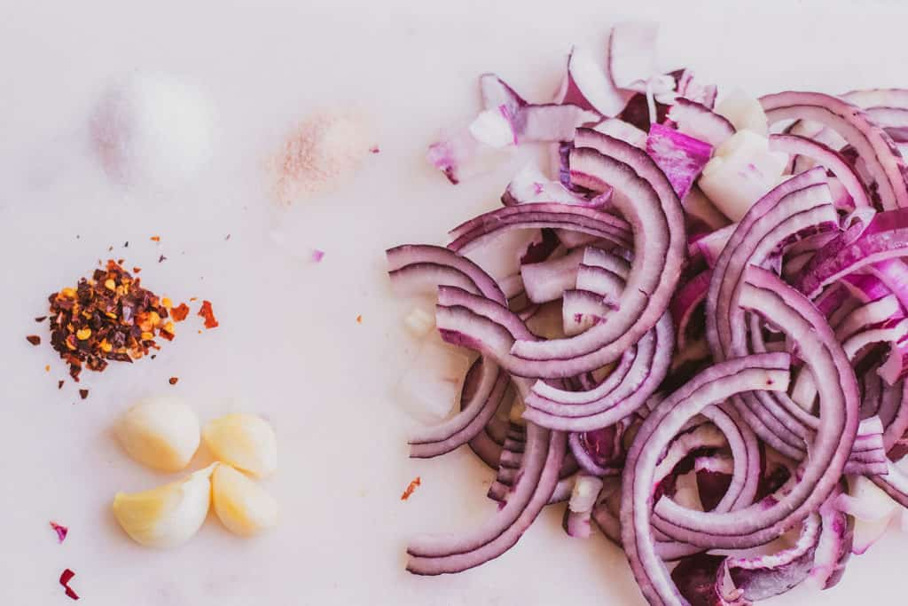 The ingredients for Low carb Pickled Red Onions on a white surface.
