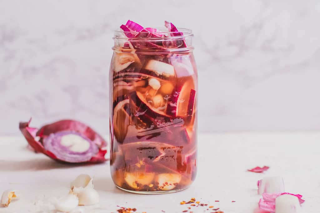 Low carb Pickled Red Onions in a mason jar on a white surface.