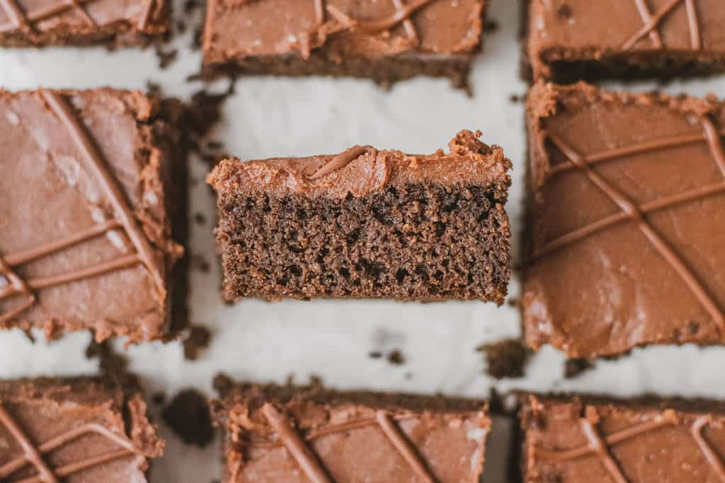 Keto chocolate sheet cake slices on a white surface.