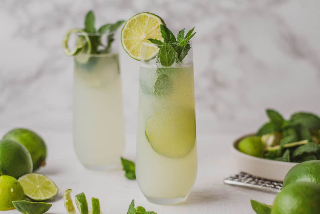 Low carb mojito with limes and mint leaves in a tall clear glass on a white surface.