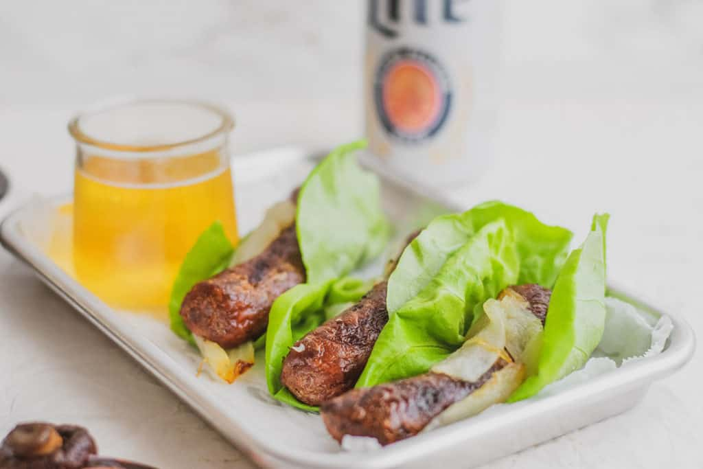 Low carb Wisconsin Beer Brats on a lettuce wrap with Miller Lite in the background on a white surface.