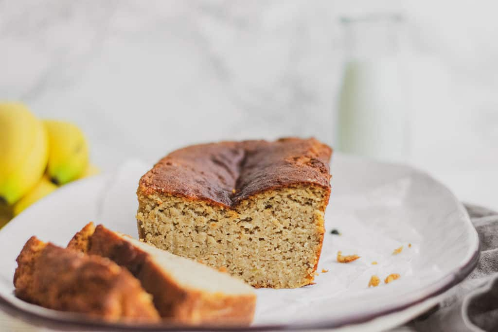 Keto Banana Bread loaf sliced on a white plate with bananas in the background.