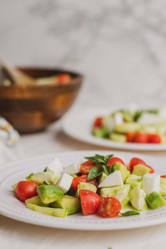 Fresh keto Tomato Cucumber Salad on a white plate on a white surface.