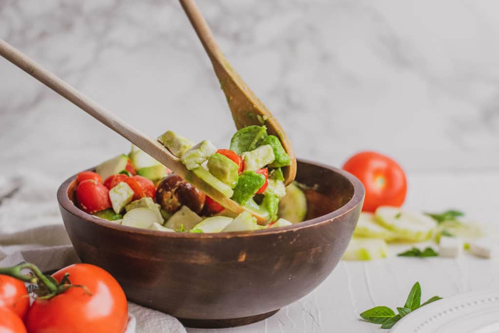 Fresh keto Tomato Cucumber Salad in a wood bowl on a white surface with wood spoons.