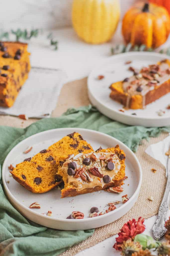 Keto Chocolate Chip Pumpkin Bread sliced on white plates with a green napkin on the side.