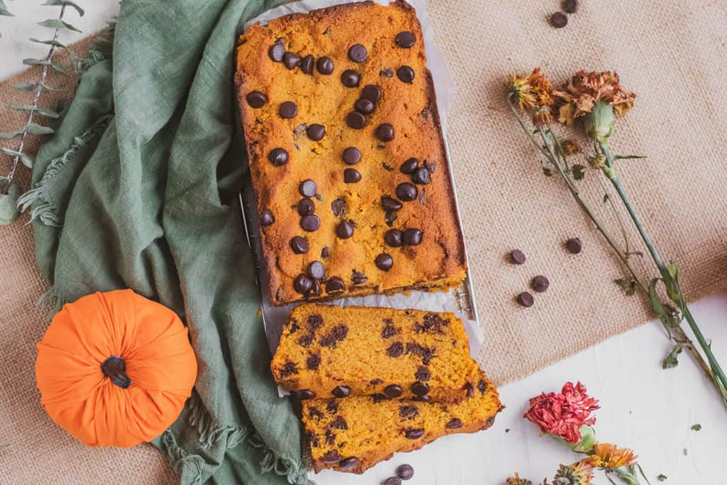 Keto Chocolate Chip Pumpkin Bread sliced loaf with a green napkin on the side.