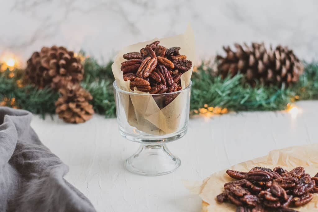 Keto Candied Pecans in a glass cup with garland and pine cones in the background on a white surface.