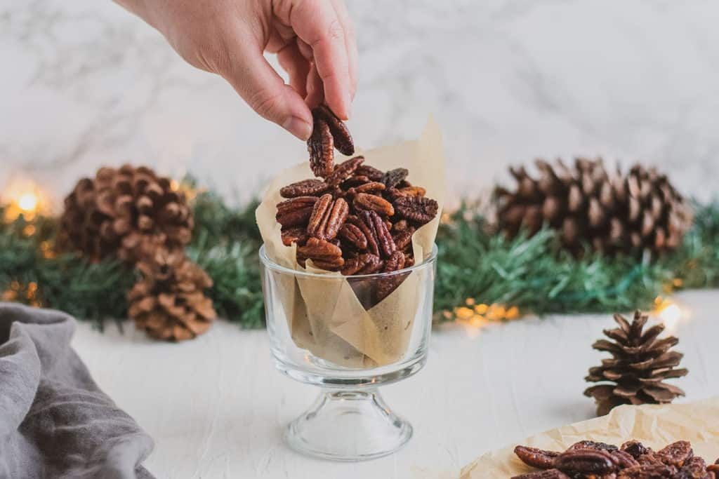 Keto Candied Pecans in a glass cup with a  hand taking a few with garland and pine cones in the background on a white surface.