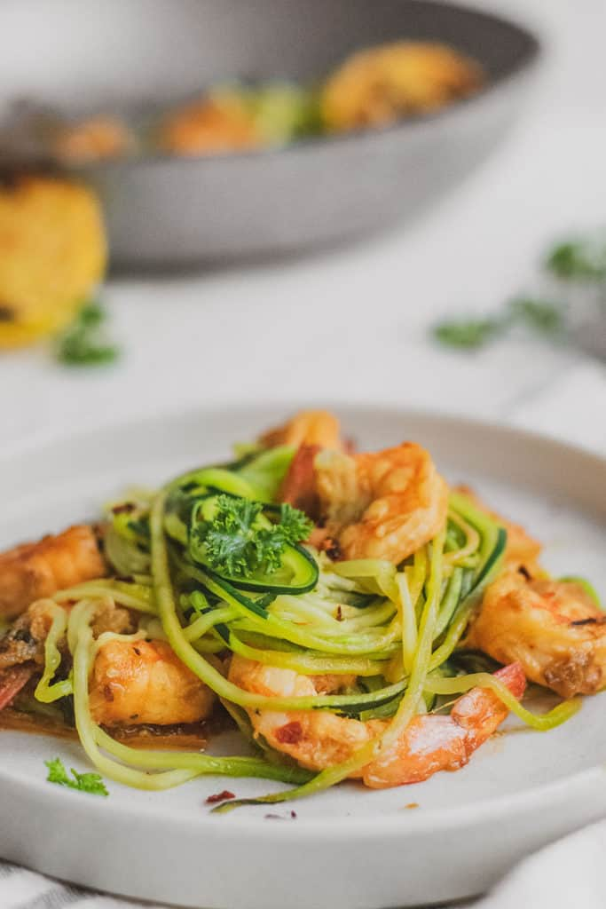 Keto shrimp scampi with zucchini noodles, shrimp, and parsley on a white plate with a grilled lemon and napkin on the side.