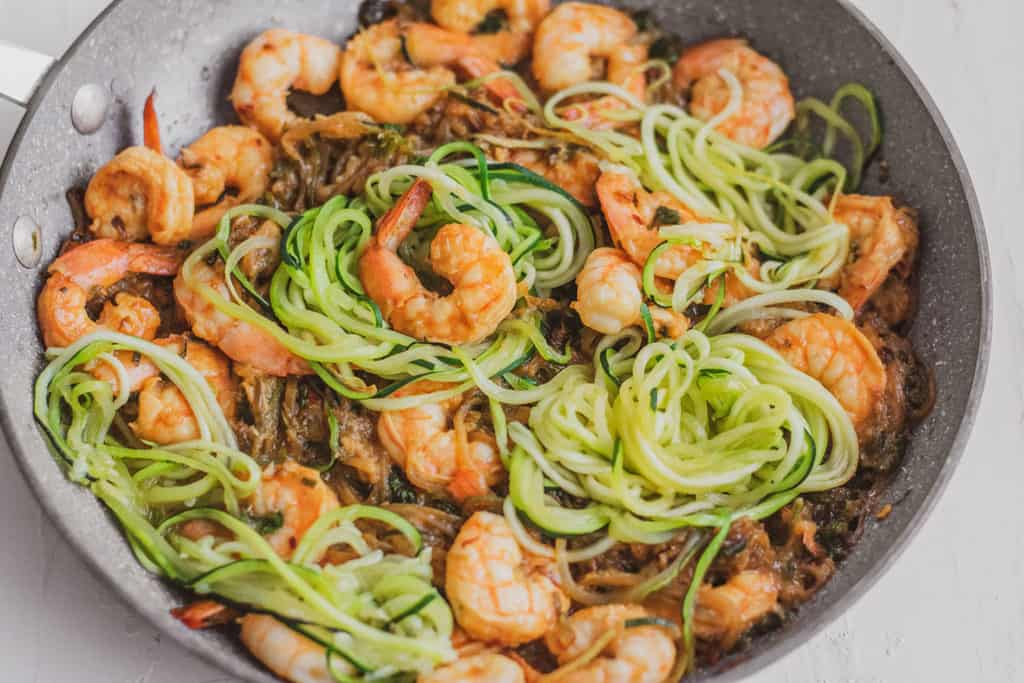 Keto shrimp scampi with zucchini noodles, shrimp, and parsley is a grey skillet.