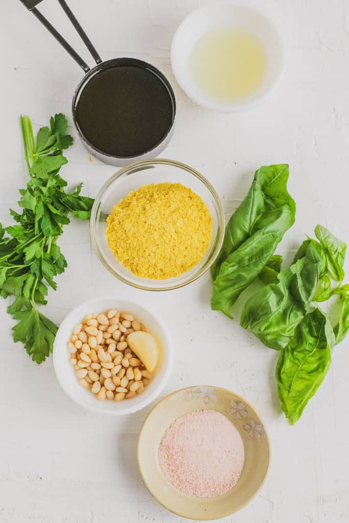 All of the ingredients you need to make basil pesto in separate little bowls on a white surface.