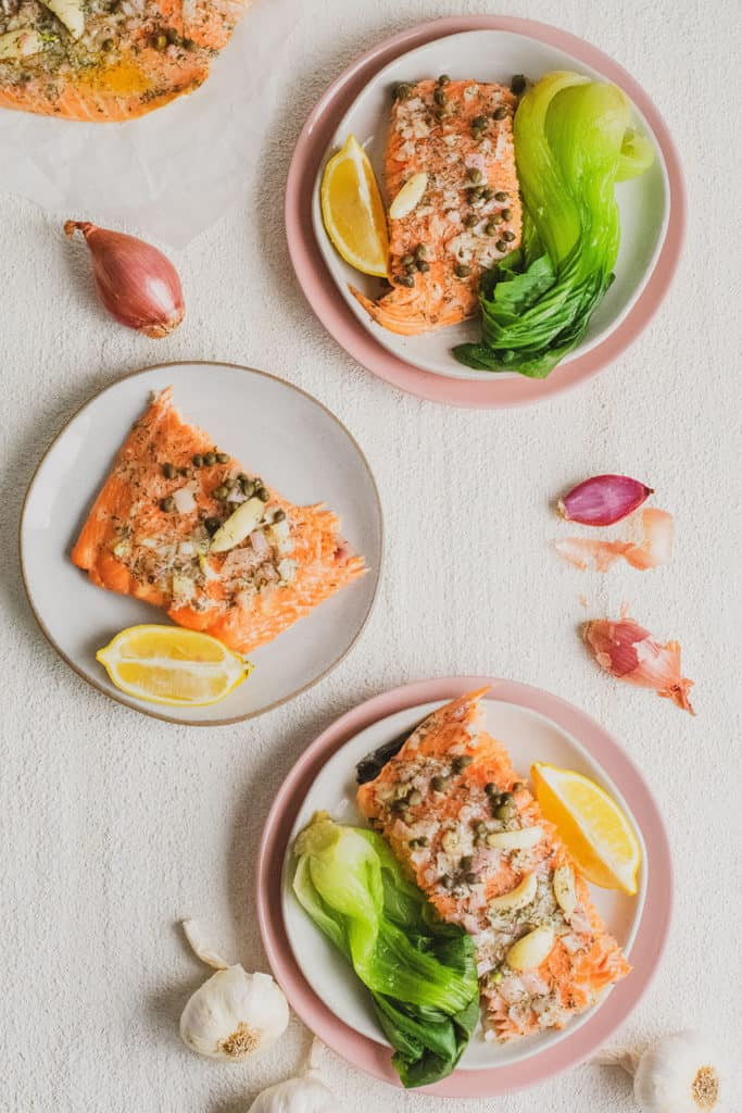 Keto Garlic Butter Baked Salmon fillets on white plates and pink plates under on a white surface with a side of bok choy and a lemon wedge and shallots and garlic bulbs on the side.
