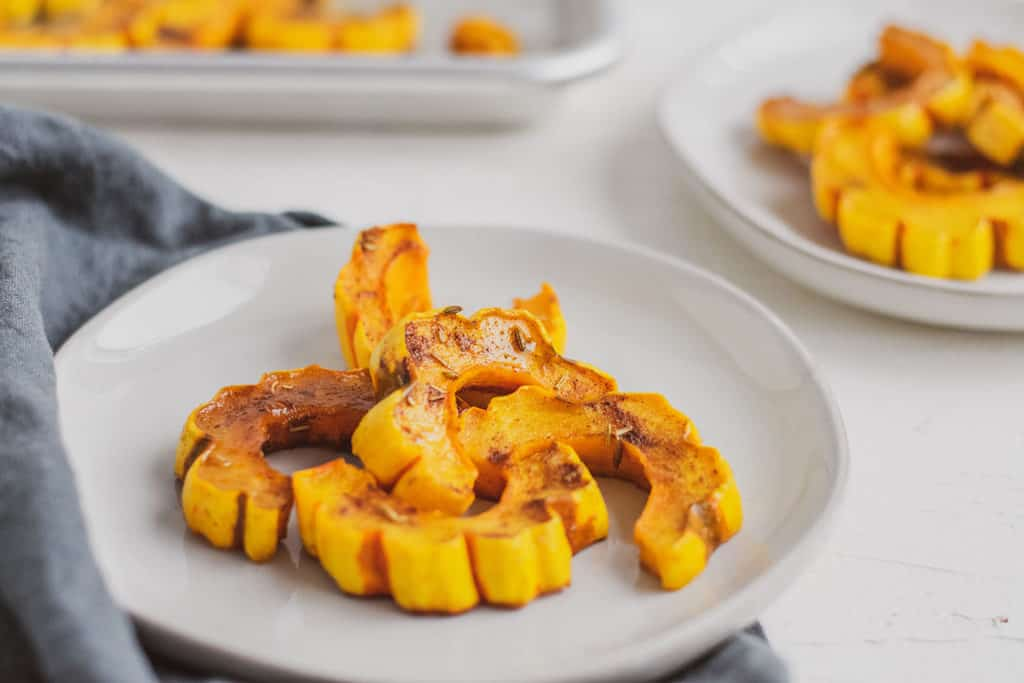 Keto roasted delicata squash on a white plate and surface.