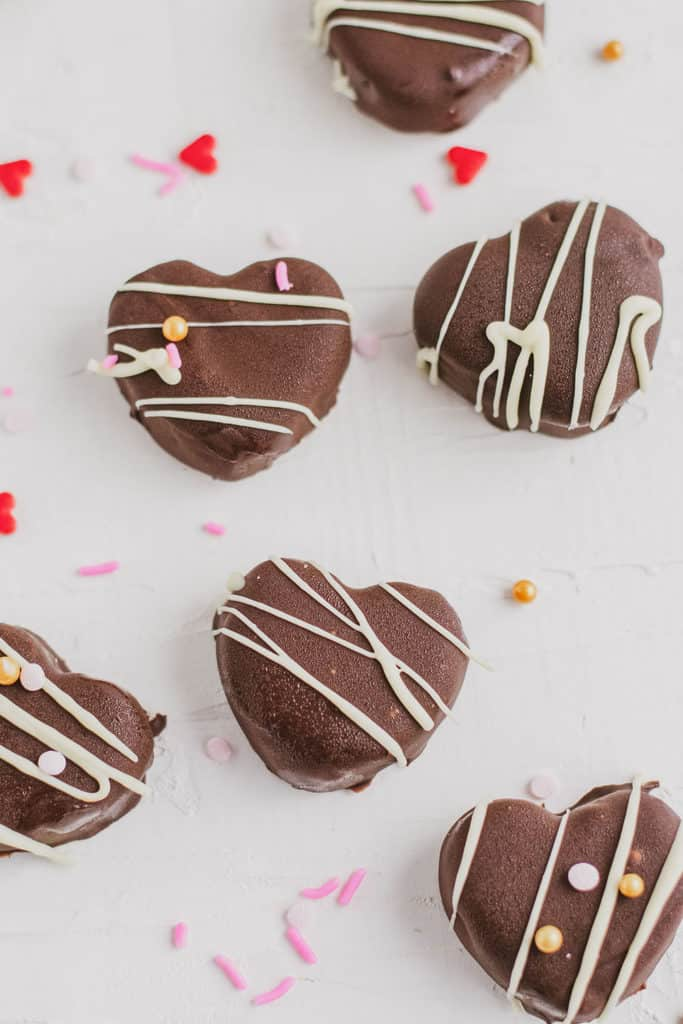 Keto Peppermint Patties shaped as a heart that are chocolate coated with white chocolate drizzle and heart sprinkles on a white surface.