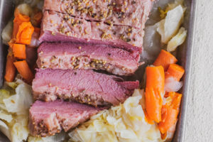 Sliced Keto Corned Beef and Cabbage on a tray with cooked carrots and onions on the side on a white surface