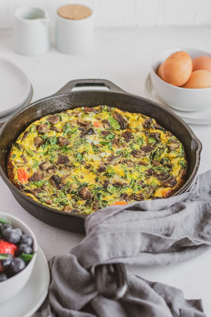 Keto Kale and Mushroom Frittata in a skillet with a blue napkin and a bowl of berries on the side