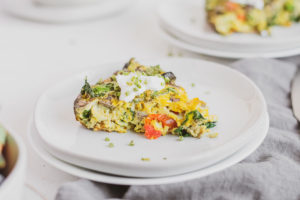 Keto Kale and Mushroom Frittata slice on a white plate with a blue napkin on the side
