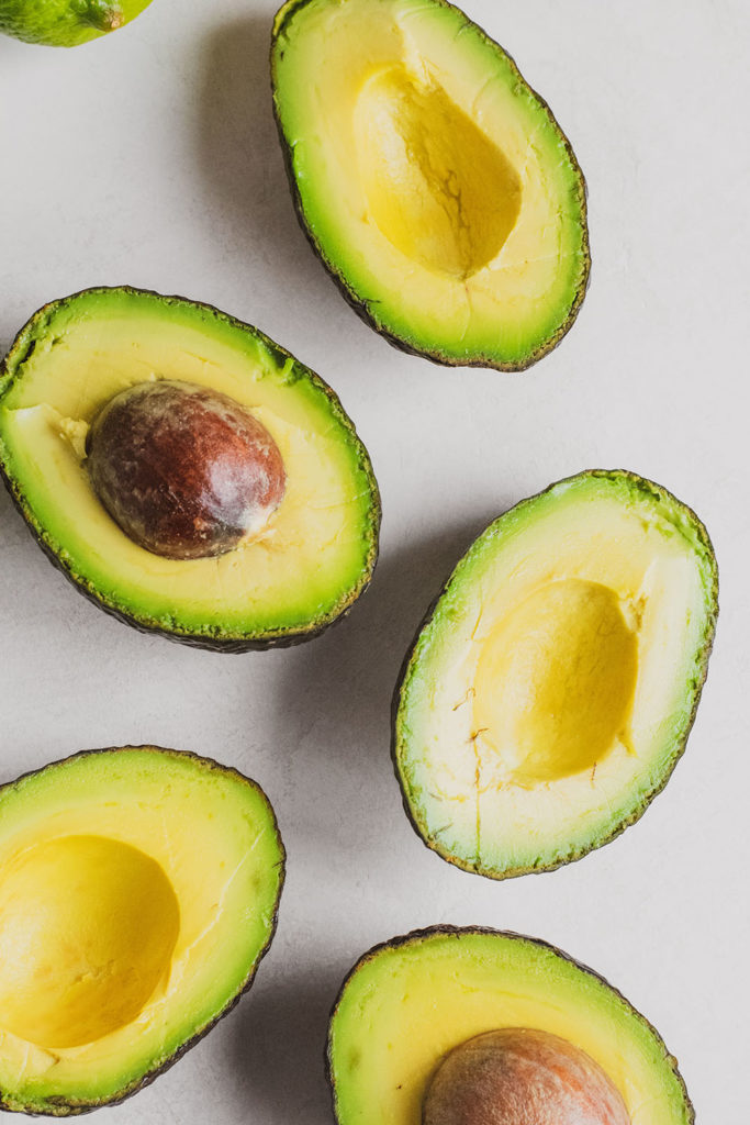 Cut in half avocados on a white surface