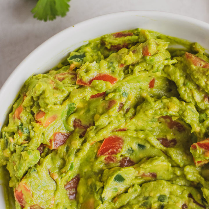 Keto homemade guacamole in a white bowl with a black fork on a white surface