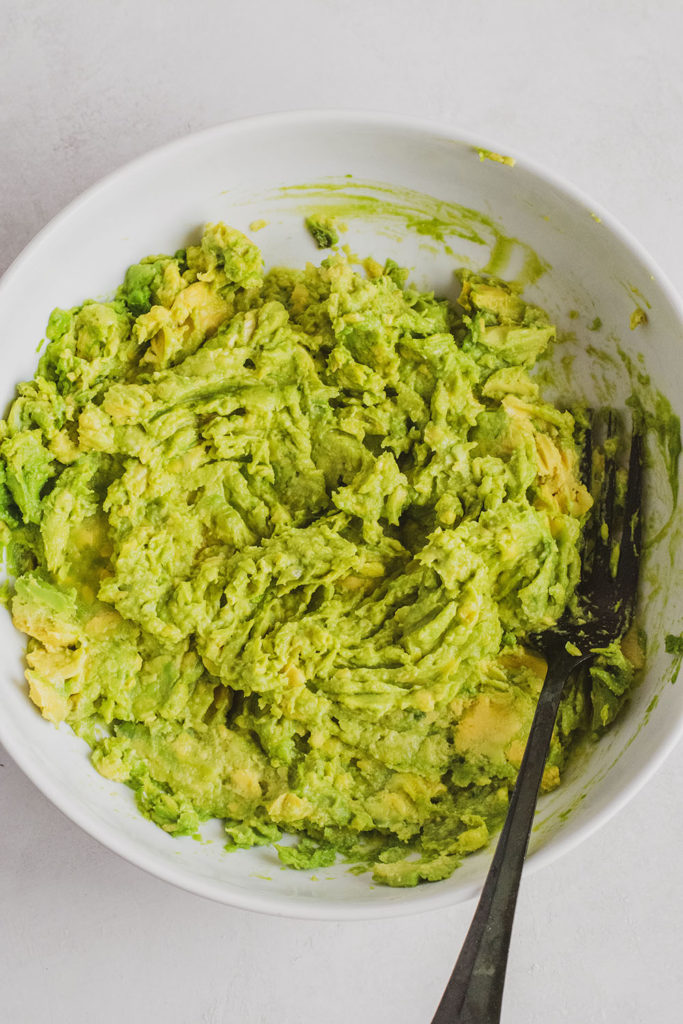Keto homemade guacamole mashed up in a white bowl
