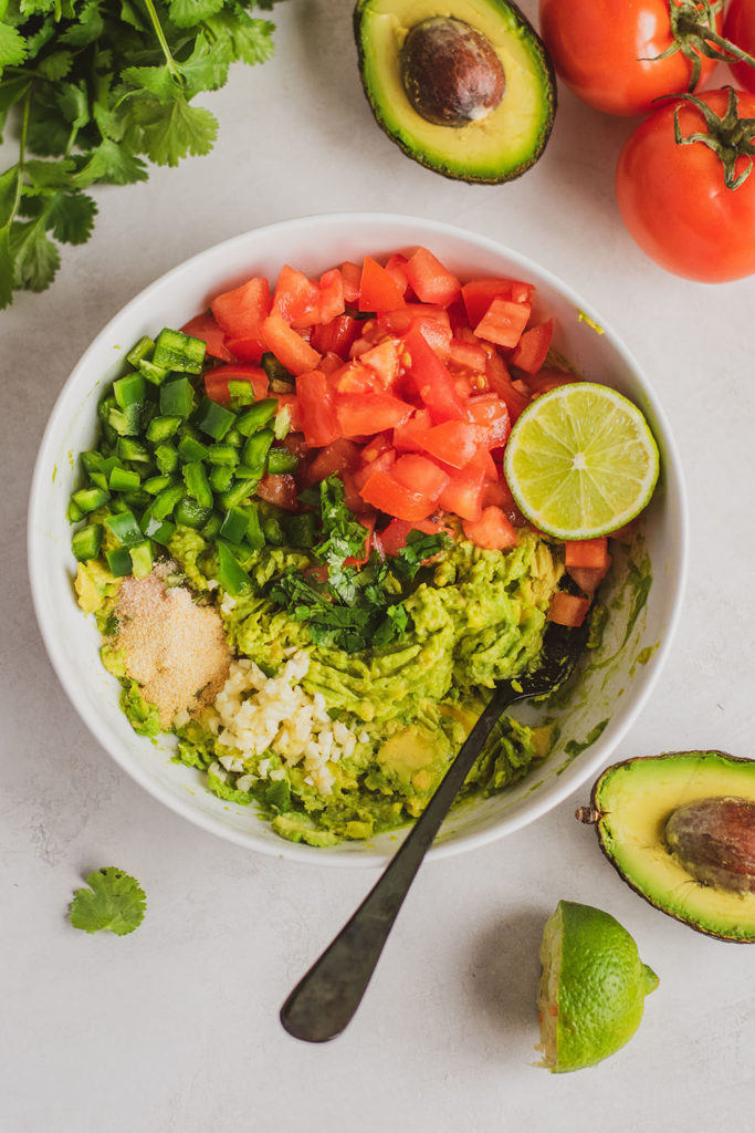 Keto homemade guacamole ingredients in a white bowl with a black fork